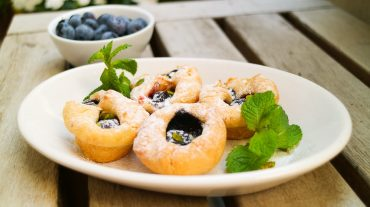 Heidelbeeren die auch Blaubeeren heißen sind eine leckere Basis für Muffins. Muffins auf einem Teller angerichtet.