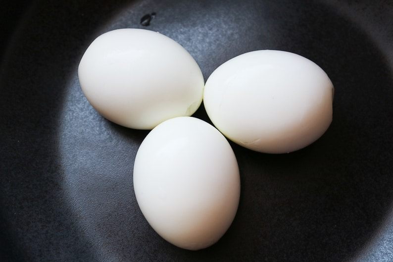 Gekochte und geschälte eier auf einem schwarzen teller fotografiert