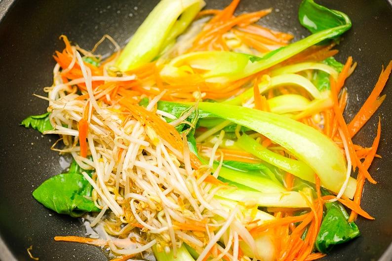 Gemüse in der Pfanne gedünstet: Karottenstreifen, Pak Choi, Sojasprossen.