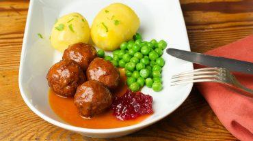 Köttbullar mit Erbsen und Kartoffeln, Rahmsauce und Preiselbeeren.