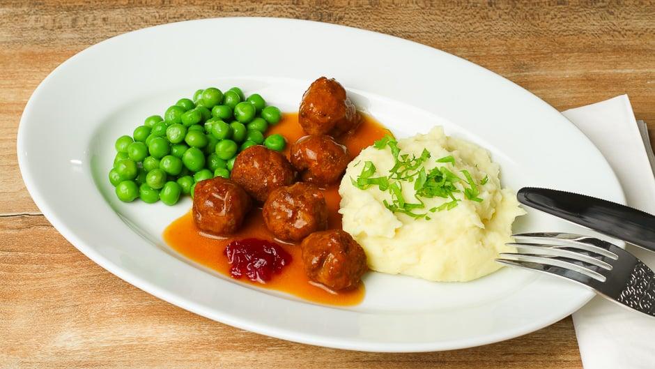 Köttbullar angerichtet auf einem Teller mit Erbsen, Kartoffelpüree, Rahmsoße und Preiselbeeren.