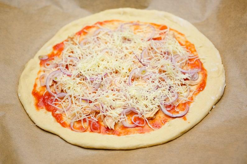 Käse auf die Thunfischpizza legen.