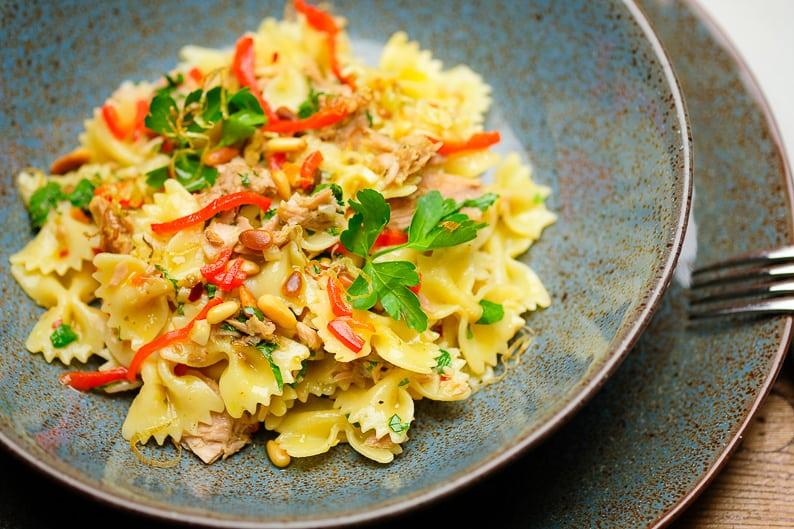 Nudeln mit Thunfisch, Knoblauch, Petersilie angerichtet in einem tiefen Teller.