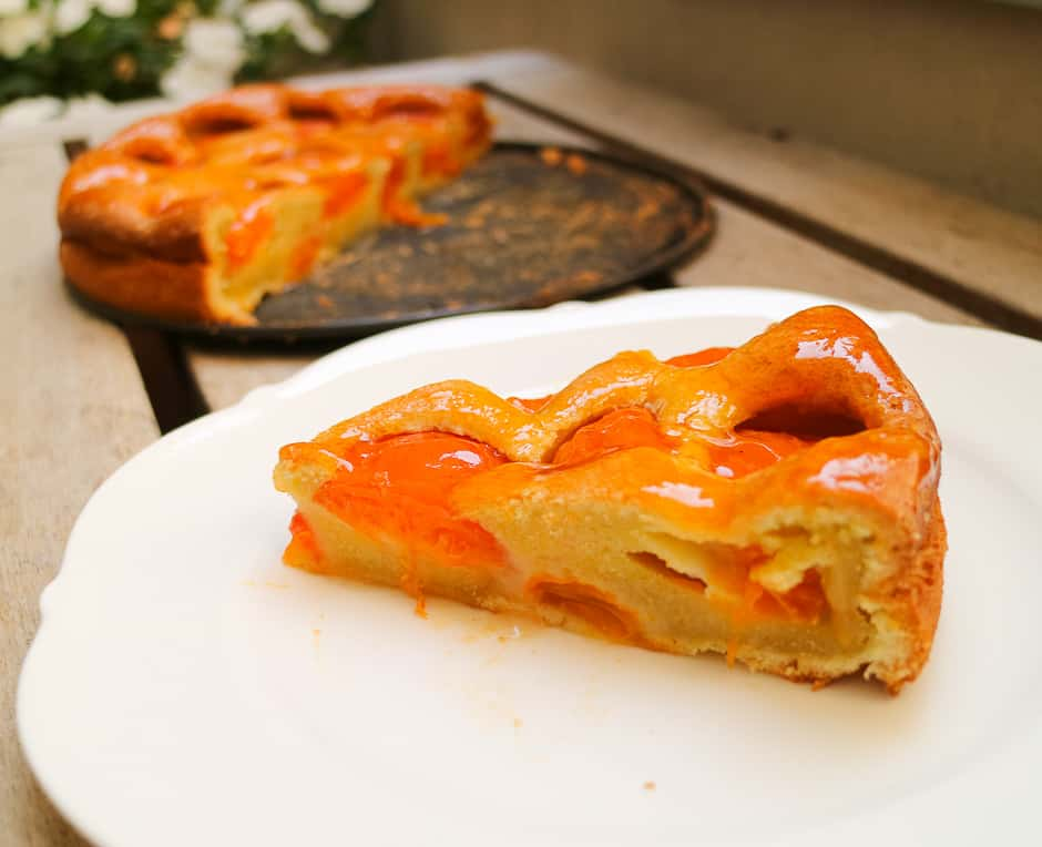 Apricot cake cut open, cake surface and fruits shine.