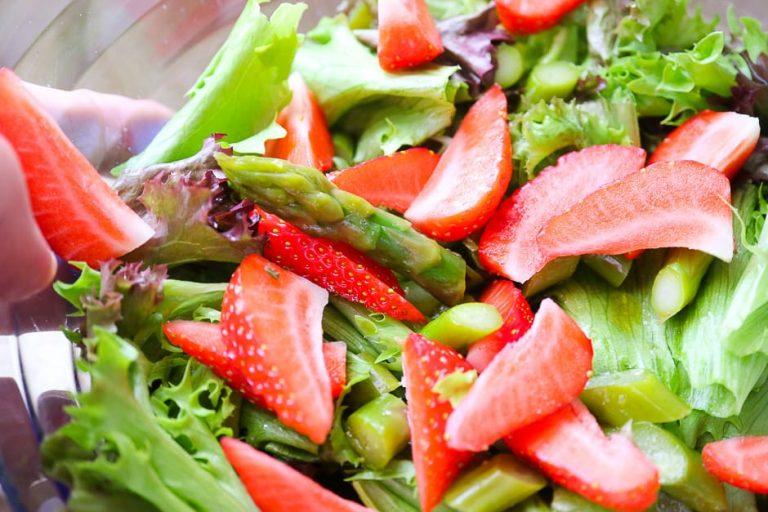 Spargel und Erdbeeren vorbereitet mit Blattsalaten.