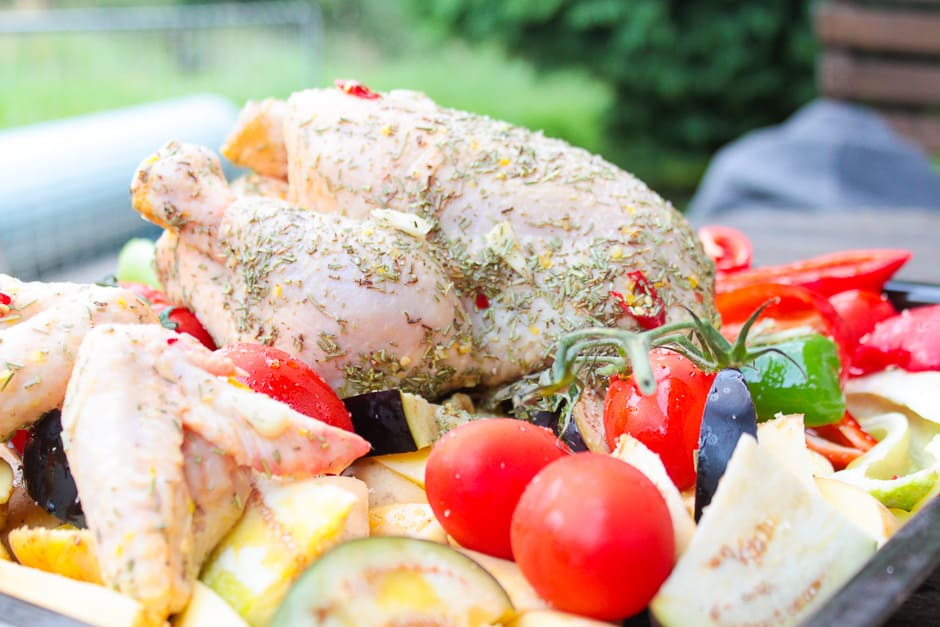 Roast chicken marinated raw with vegetables, prepared for the oven.