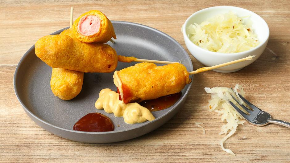 Corn Dogs anrichten und mit kalten dips und Soßen servieren.