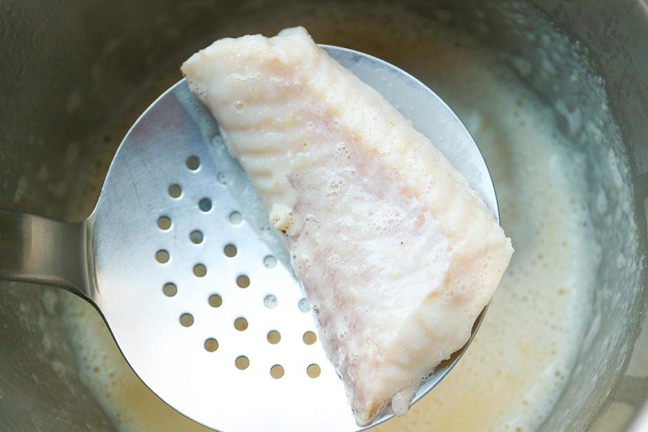 Pochierter Fisch über der Senfsoße fotografiert liegend auf einer Schaumkelle.