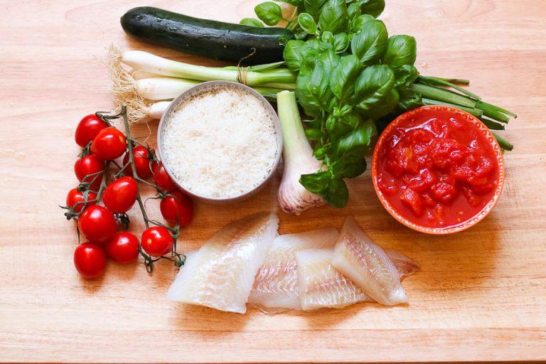 Zutaten für Fisch mit Beilage Reis auf dem Küchenbrett.