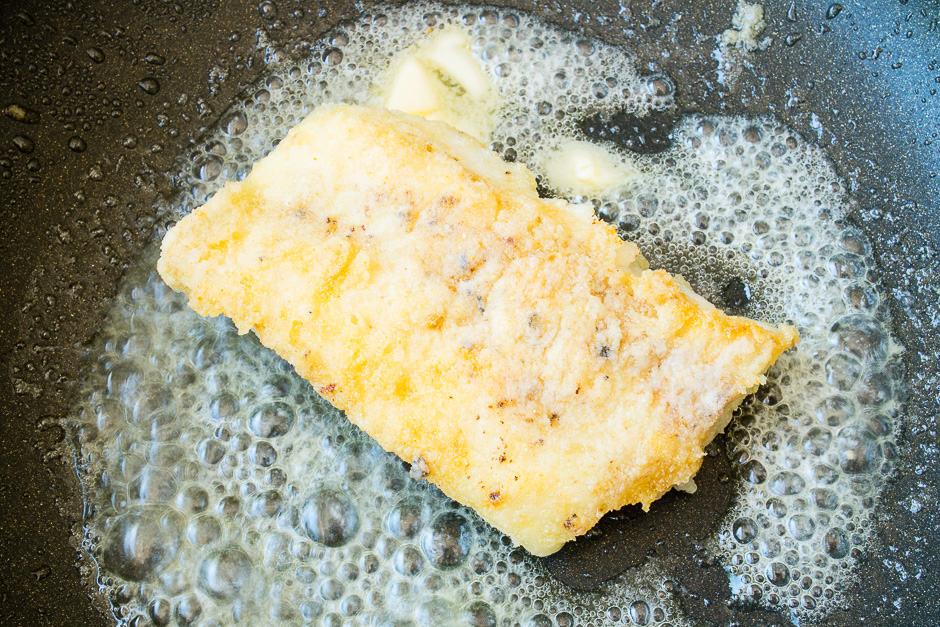 Fischfilet in der Pfanne mit aufgeschäumter Butter.