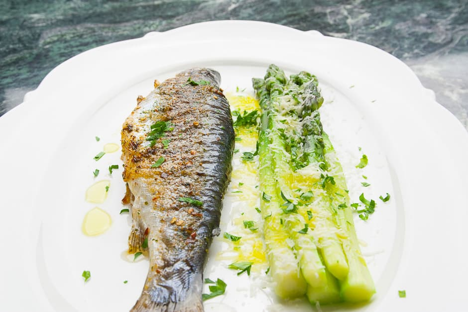 Trout served whole with asparagus.