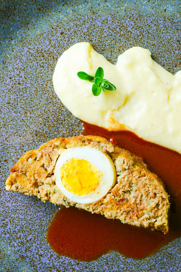 Hackbraten alias Falscher Hase angerichtet auf einem Teller mit Soße und Kartoffelpüree.