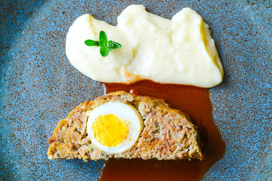 Meat loaf with egg, sauce and mashed potatoes on a blue plate.