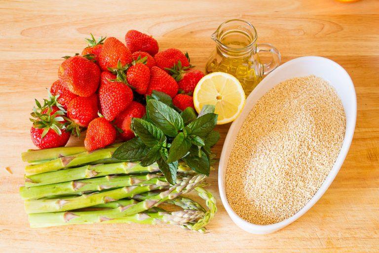 Quinoa Salat Zutaten Spargel, Erdbeeren auf einem Küchebrett.
