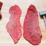 Roulade zubereiten, Fleich von der Rinderoberschale auf einem Küchenbrett beim Klopfen.