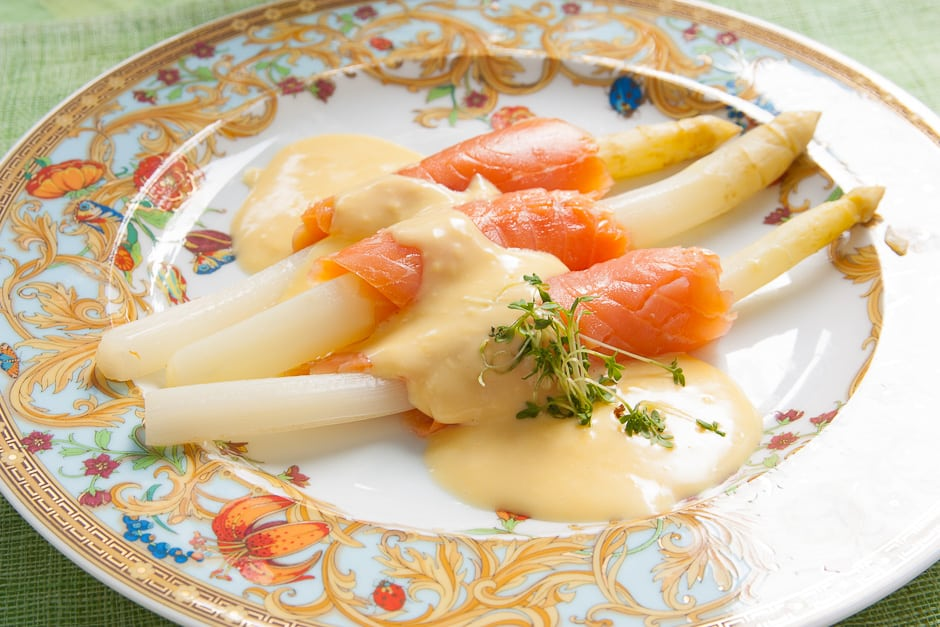 white asparagus with smoked salmon served with sauce hollandaise.