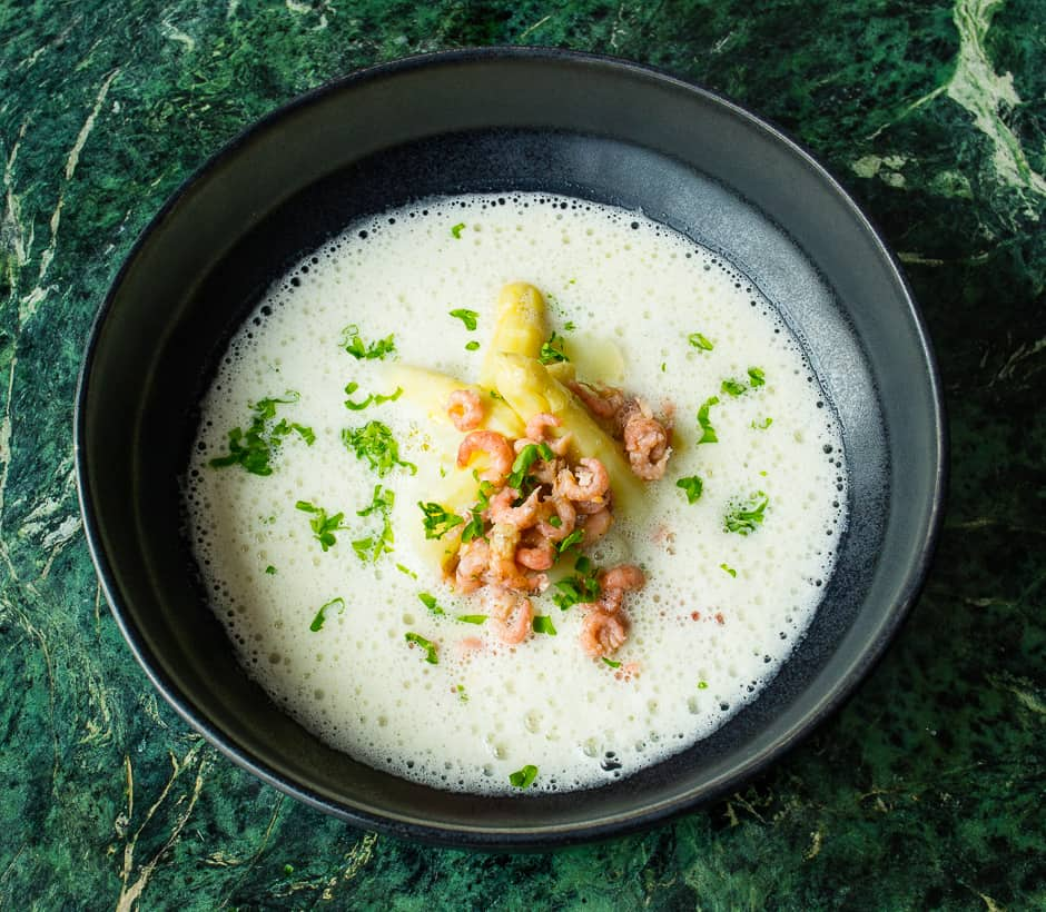 Cream of asparagus soup served with asparagus pieces, shrimps and parsley.