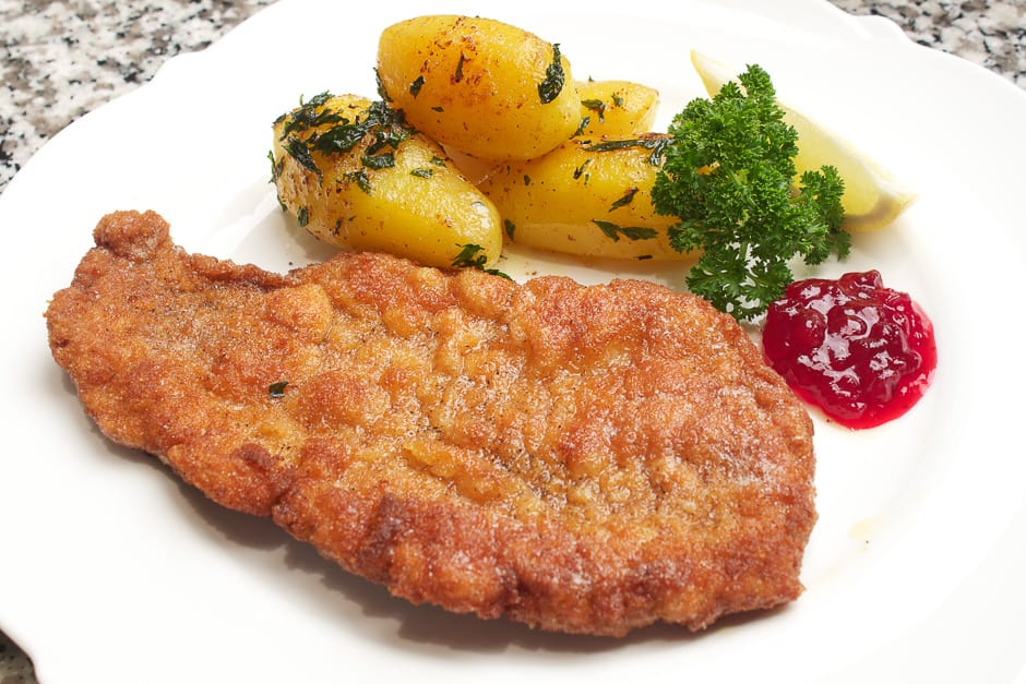 Wiener Schnitzel served on a plate with cranberries and parsley potatoes.