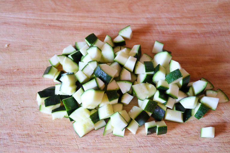 Zucchini, gewürfelt auf einem Brett fotografiert.