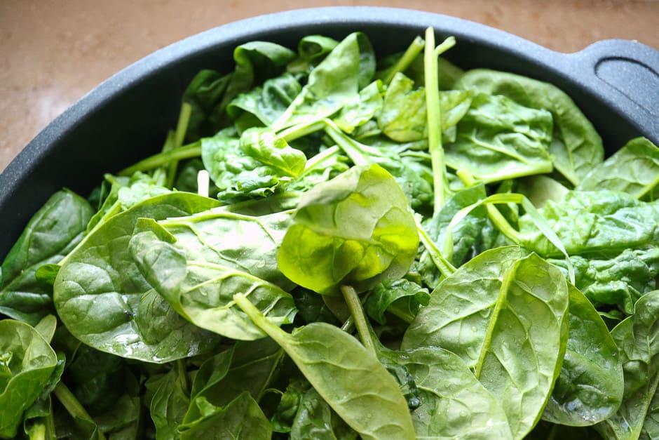 Spinat mit Zwiebeln und Knoblacuh zusammen im Topf.