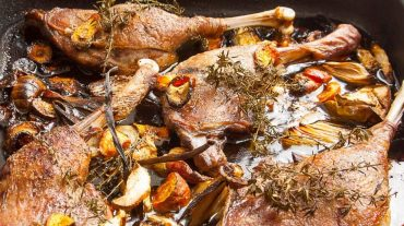 Rezept Bild zu Gebratene Entenkeulen mit Gemüse aus dem Backofen. Knusprig gegarte Keule von der Ente mit Gemüse und Beilagen.