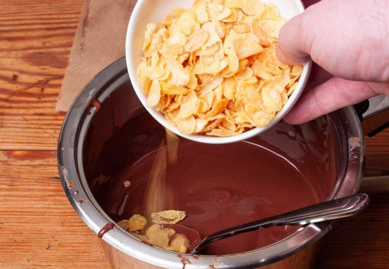Cornflakes zur geschmolzenen Schokolade geben