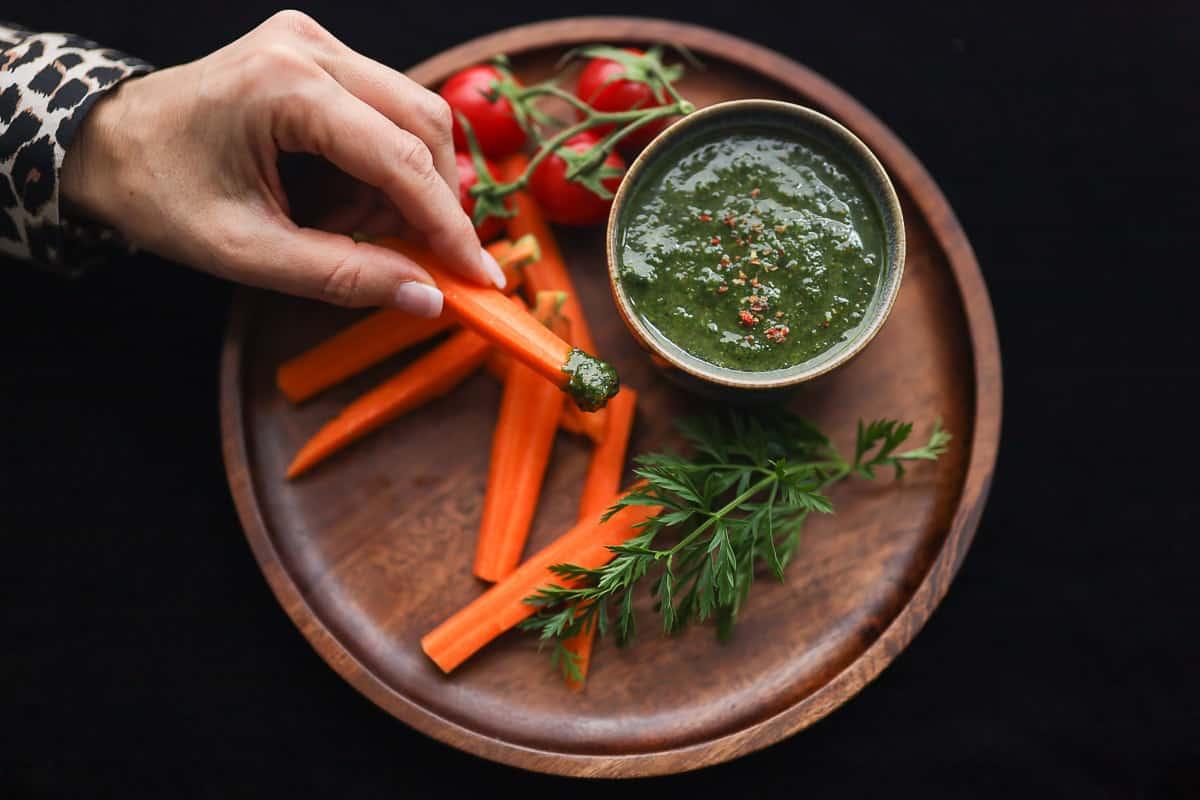 Karotte beim dippen in Karottengrün Pesto