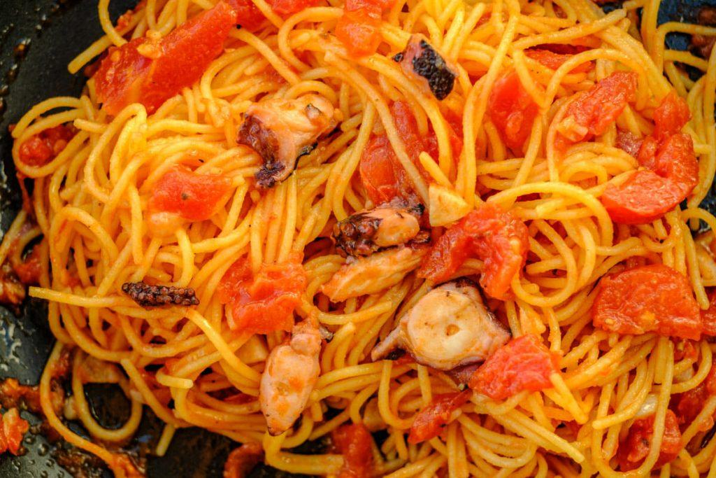 Spaghetti mit Pulpo und Tomatensauce vermischt